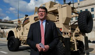 Ashton Carter, undersecretary of defense for acquisition, technology and logistics, discusses a mine-resistant ambush-protected armored fighting vehicle at the Pentagon. President Obama wants to promote the weapons buyer, but Mr. Carter has done some consulting work for the defense industry. (Associated Press)