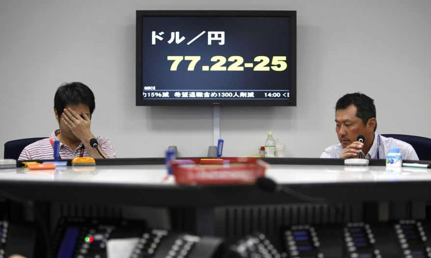Money traders work Aug. 3, 2011, in front of the electric board showing the yen-dollar exchange rate at a money market brokerage firm in Tokyo.