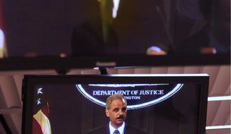 Attorney General Eric H. Holder Jr. is seen on multiple television screens, at Justice Department on Wednesday during a news conference to discuss results of the U.S. prosecution of an international criminal network organized to sexually exploit children. (Associated Press)