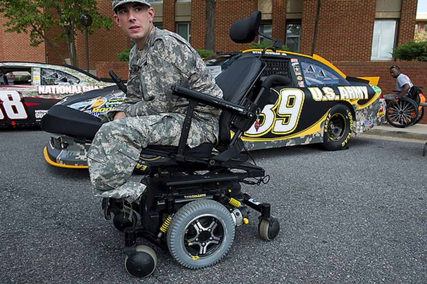 """""""They can take my legs, but they can't take my pride,"""" says Brooklyn, N.Y. native and U.S. Army PFC Bryan Dilberian, who has been at Walter Reed Army Medical Center for a month and says he can't wait to redeploy to Afghanistan. PFC Dilberian was among the wounded warriors who came out to check out the NASCAR cars at Walter Reed Army Medical Center in the District on Thursday. Several NASCAR drivers visited the facility. The event ended with a dinner and a concert by singer Billy Ray Cyrus. (Barbara L. Salisbury/The Washington Times)"""