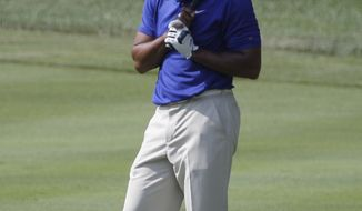Tiger Woods reacts in the 16th fairway as his fairway shot went into the green side bunker during third round play in the Bridgestone Invitational at Firestone Country Club in Akron, Ohio on Saturday. (AP Photo/Amy Sancetta)