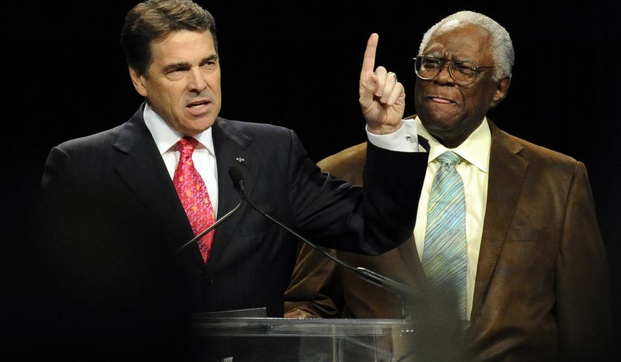 Texas Gov. Rick Perry, left, standing beside Pastor C. L. Jackson of the Pleasant Grove Missionary Baptist Church speaks at The Response, a daylong prayer and fast rally Saturday, Aug. 6, 2011, at Reliant Stadium in Houston. (AP Photo/Pat Sullivan)