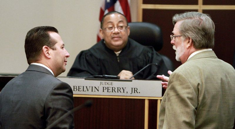ASSOCIATED PRESS PHOTOGRAPHS Casey Anthony's defense team, Jose Baez and Cheney Mason, confers with Judge Belvin Perry during a hearing at the Orange County courthouse on Friday. Judge Perry is deciding whether Casey Anthony has to return to Florida to serve probation for check fraud. Miss Anthony did not attend the hearing.