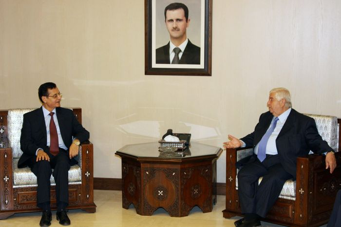 """ASSOCIATED PRESS Syrian Foreign Minister Walid al-Moallem (right) met with his Lebanese counterpart, Adnan Mansour, in Damascus, Syria, on Sunday. Mr. Mansour also met with Syrian President Bashar Assad (shown in portrait), who has stressed that his country is moving steadily on reforms but would deal with """"outlaws"""" to preserve the country's security."""