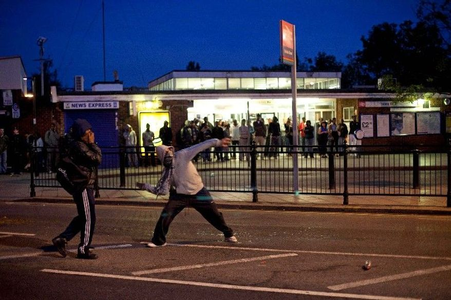 Youths hurl bricks at police Sunday during unrest in Enfield, north London. Sky News television reported that several hundred people were causing trouble.