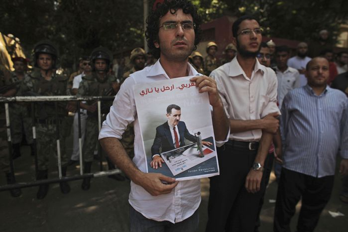 A Syrian demonstrating in Cairo on Friday, Aug. 5, 2011, holds up a poster with an image of Syrian President Bashar Assad during a protest against the leader's regime. (AP Photo/Tara Todras-Whitehill)