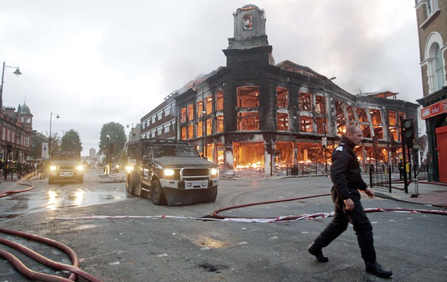 Police vehicles drive past a fire in a building in Tottenham.  One police officer was hospitalized and seven others were injured during riots when a north London suburb exploded in anger Saturday night.    (AP Photo/Lewis Whyld/PA Wire)