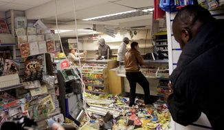 ASSOCIATED PRESS PHOTOGRAPHS  People loot a shop (left) in the  east London borough of Hackney on Monday. Rioting in London continued for a third day, spreading throughout the city after a peaceful protest Saturday turned violent. More than 200 people have been arrested, and 35 police officers have been injured. British police officers arrest a man (above) as rioters gather in Croydon, south London, on Monday.