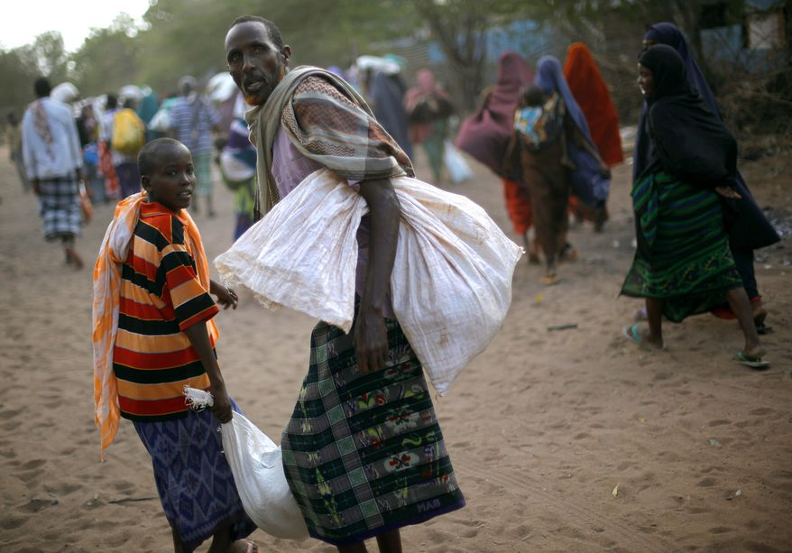 Somali refugees carry their donated rations of food aid on Aug. 7, 2011, in the eastern Kenyan village of Hagadera near Dadaab, 60 miles from the Somali border. (Associated Press)