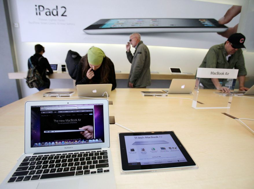 ** FILE ** Apple customers look at the Apple MacBook Air in San Francisco. (Associated Press)