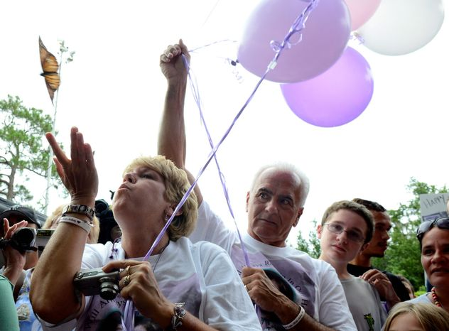 Cindy Anthony, left, blows a butterfly off her hand as George Anthony, center, watches, during a butterfly and balloon release as part of a memorial ceremony at the site where the body of their granddaughter Caylee Anthony was found on what would have been her sixth birthday in Orlando, Fla., Tuesday, Aug. 9, 2011.  Their daughter Casey Anthony was acquitted of the most serious charges related to the death of her daughter Caylee Anthony. (AP Photo/Phelan M. Ebenhack)