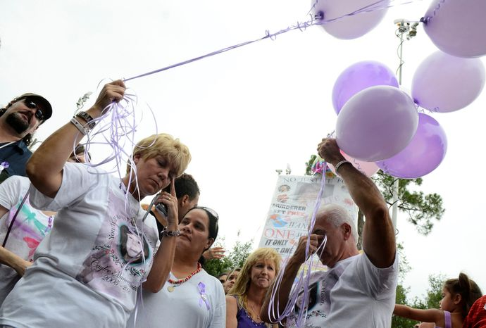 Cindy Anthony, second from left, and George Anthony, second from right, wipe away tears during a memorial ceremony at the site where the body of their granddaughter Caylee Anthony was found on what would have been her sixth birthday in Orlando, Fla., Tuesday, Aug. 9, 2011.  Their daughter Casey Anthony was acquitted of the most serious charges related to the death of her daughter Caylee Anthony. (AP Photo/Phelan M. Ebenhack)