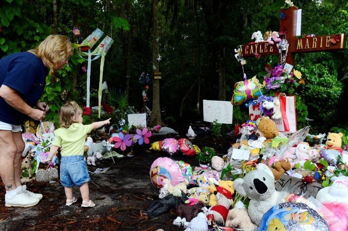 Hailey Murray, 2, and her grandmother Kimberly Rikard, of Cocoa Beach, Fla., visit a makeshift memorial for Caylee Anthony on what would have been her sixth birthday, in Orlando, Fla., Tuesday, Aug. 9, 2011.  The site has become a place for mourners and followers of the case to leave wishes and mementos.  Casey Anthony was acquitted of the most serious charges related to her daughter Caylee Anthony's death. (AP Photo/Phelan M. Ebenhack)