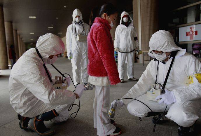 **FILE** In this photo from March 24, 2011, a young evacuee is screened at a shelter for leaked radiation from the damaged Fukushima nuclear plant in Fukushima, Fukushima prefecture, Japan. (Ass