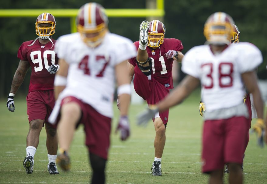 Washington Redskins linebacker Ryan Kerrigan (91) kicks his leg as he and fellow Redskins players run through drills on Tuesday, Aug. 9, 2011. (Rod Lamkey Jr./The Washington Times)