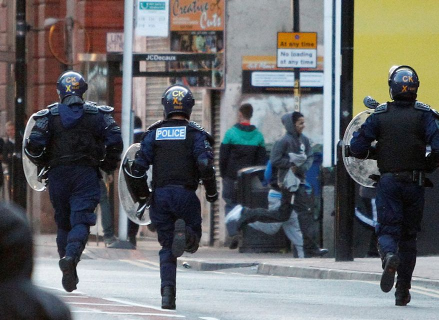 Riot police chase alleged looters during civil disturbances in Manchester, England.  Three nights of looting and burning by crowds of young people appears to have spread from the capital to other locations in Britain. (AP Photo/Jon Super).