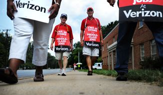 Phil Hart (left) and Clinton Jennings walk the picket line on Aug. 8, 2011, during the Communication Workers of America strike outside Verizon on Leesville Road in Lynchburg, Va. (Associated Press/The News & Advance)