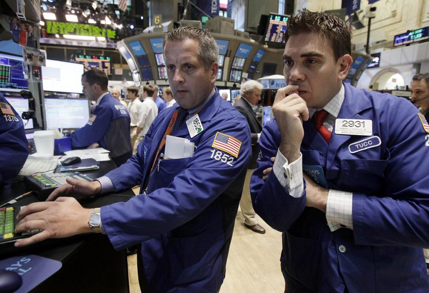 Specialists Donald Vaneck (center) and Robert Tuccillo work on the floor of the New York Stock Exchange on Aug. 9, 2011. (Associated Press)