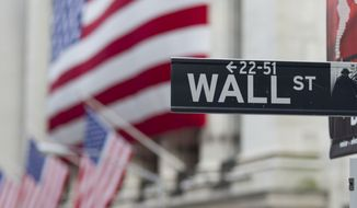 A Wall Street sign hangs near the New York Stock Exchange in New York. (AP Photo/Jin Lee)