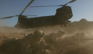 **FILE** U.S. soldiers from the 2nd Brigade, 87th Infantry Regiment, 10th Mountain Division, secure the area after exiting a Chinook helicopter, Helmand Province, southern Afghanistan, on June 18, 2006. Insurgents shot down on Aug. 6, 2011, a U.S. military helicopter similar to this one shown during fighting in eastern Afghanistan, killing 30 Americans, most of them belonging to the same elite Navy SEALs unit that killed Osama bin Laden, as well as seven Afghan commandos, U.S. officials said. (Associated Press)