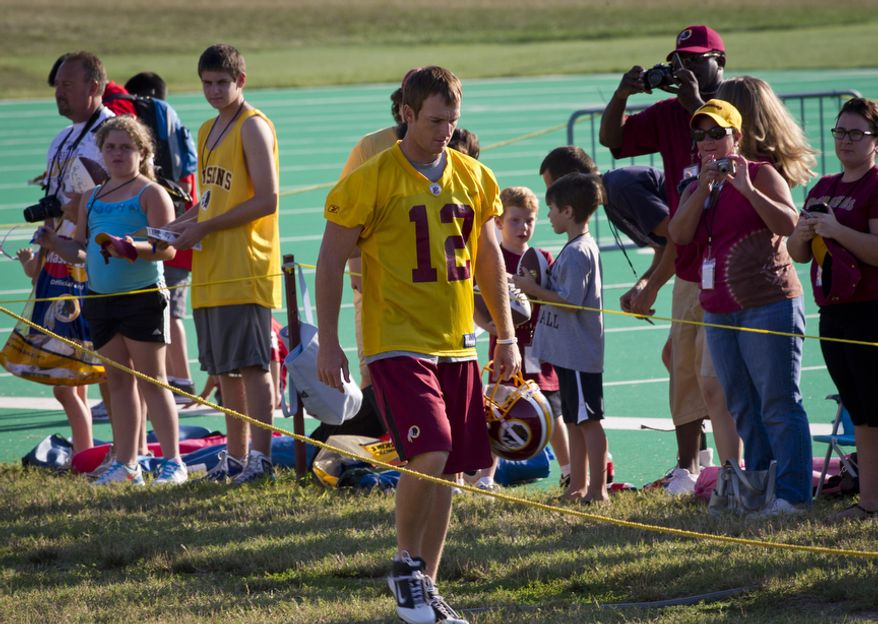Washington Redskins quarterback John Beck (No. 12) arrives on the field, passing by a line of fans, during training camp at Redskins Park in Ashburn, Va, Wednesday, August 10, 2011. (Rod Lamkey Jr./The Washington Times)