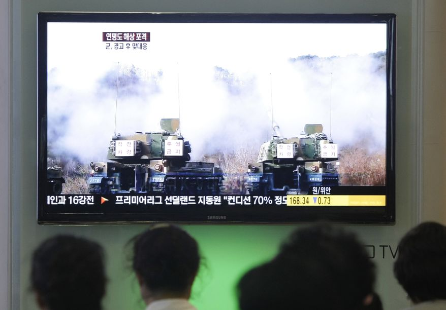 South Koreans at Seoul's main railroad station watch a TV news program on Wednesday, Aug. 10, 2011, showing file video footage of South Korean army K-9 self-propelled howitzers during a previous military exercise. The South's marines returned fire Wednesday after North Korea launched artillery shells into waters near the disputed maritime line that separates the two rivals, South Korean defense officials said. (AP Photo/Ahn Young-joon)