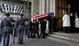 The flag-draped coffin carrying former New York Gov. Hugh Carey is taken down the steps of St. Patrick's Cathedral in New York City on Thursday. The seven-term congressman, who as governor led New York out of an economic crisis in the 1970s, died Sunday at the age of 92. (Associated Press)