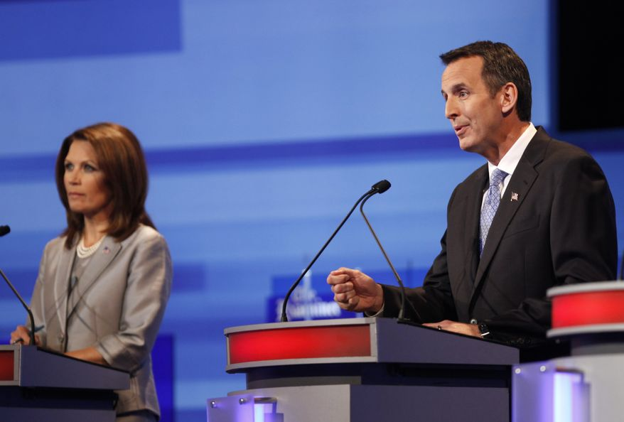 Republican presidential candidates former Minnesota Governor Tim Pawlenty speaks as Rep. Michele Bachmann, Minnesota Republican, listens during the Iowa GOP/Fox News Debate at the CY Stephens Auditorium in Ames, Iowa, Thursday, Aug. 11, 2011. (AP Photo/Charlie Neibergall, Pool)