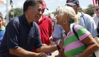 Republican presidential candidate and former Massachusetts Gov. Mitt Romney (left) campaigns at the Iowa State Fair in Des Moines, Iowa, on Aug. 11, 2011. (Associated Press)