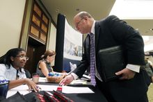 Job seeker Ted Koblick speaks with recruiter Catrina Stagnato during a Career Job Fair in Arlington, Va., on Aug. 4, 2011. (Associated Press)