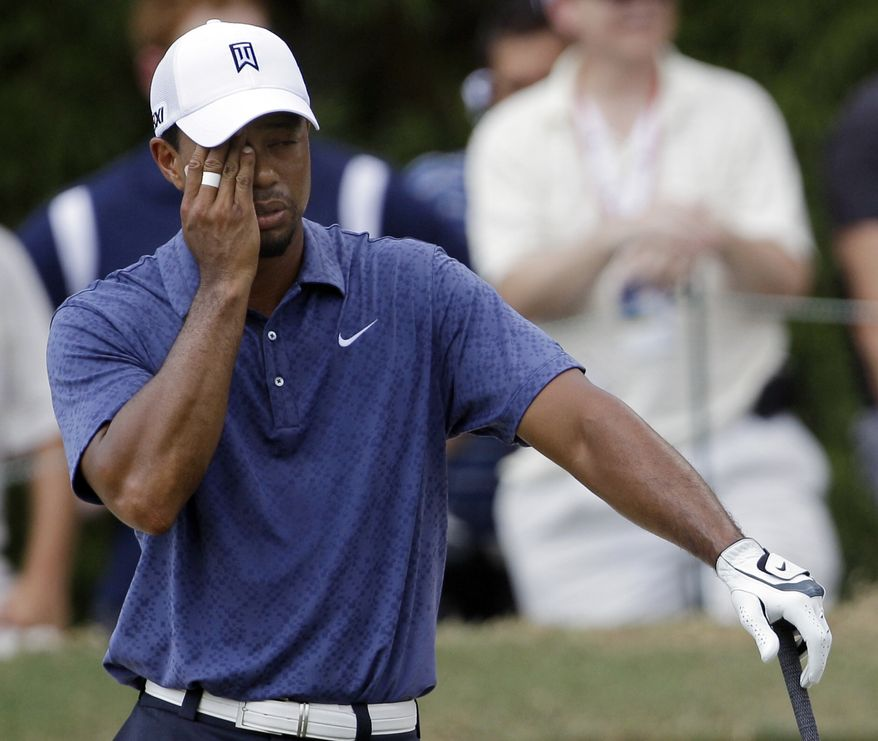 Tiger Woods reacts after hitting out of a bunker on the fifth hole during the second round of the PGA Championship on Friday, Aug. 12, 2011, at the Atlanta Athletic Club in Johns Creek, Ga. Woods missed the cut and was sent packing. (AP Photo/David J. Phillip)