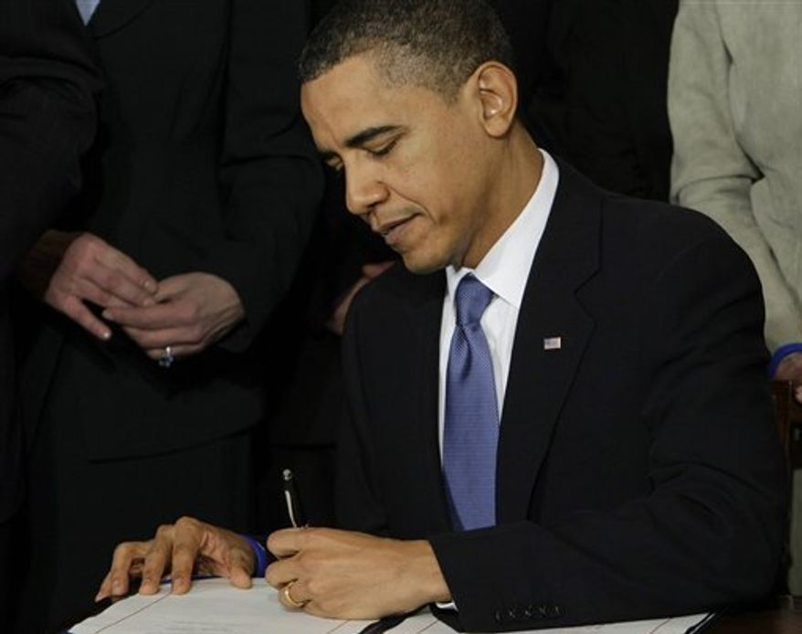 ** FILE ** President Obama signs the health care bill at the White House in Washington on March 23, 2010. (Associated Press)