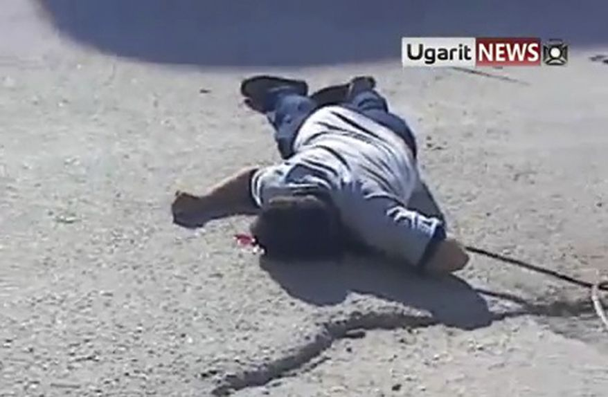 This image made from amateur video released by Ugarit News and accessed via the Associated Press Television News on Aug. 11, 2011, shows a dead body on a street in Binnish, Syria. (Associated Press/Ugarit News, via APTN)