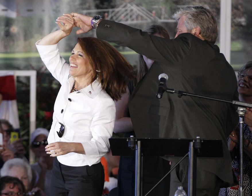 Republican presidential candidate Rep. Michele Bachmann, R-Minn. dances with her husband Marcus before speaking to her supporters at the Republican Party's Straw Poll in Ames, Iowa, Saturday, Aug. 13, 2011. (AP Photo/Charles Dharapak)