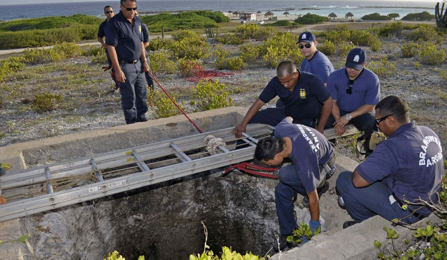 Firefighters and police officers conduct a search for Robyn Gardner, 35, of Frederick, Md., in a shaft of an old phosphate mine near Baby Beach, in the southern tip of Aruba, Friday, Aug. 12, 2011. (AP Photo/Pedro Famous Diaz)