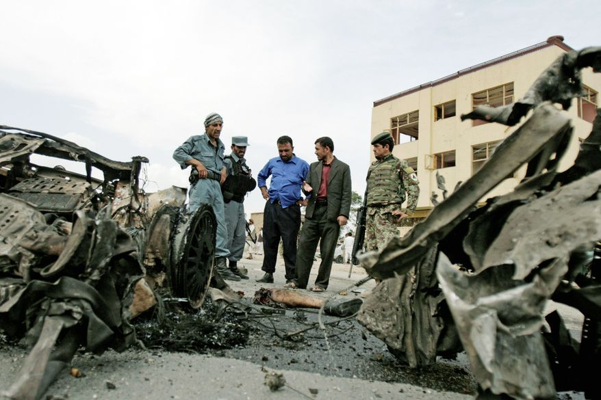 Afghan police men and Afghan soldiers inspects the site of car bomb outside governor's compound in Parwan provincial capital of Charikar, some 30 miles (50 kilometers) north of Kabul, Afghanistan, Sunday, Aug. 14, 2011. A team of six suicide bombers launched a coordinated assault on a provincial governor's compound in eastern Afghanistan on Sunday, killing 19 people in the latest high-profile attack to target prominent Afghan government officials, authorities said. (AP Photo/ Ahmad Jamshid)