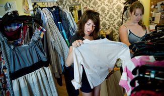 Sara Shannon, of Columbia Heights (left), and her friend Reann Anderson look over clothing on the racks at It's Vintage Darling in Columbia Heights on 14th Street in Northwest on Sunday. (Drew Angerer/The Washington Times)