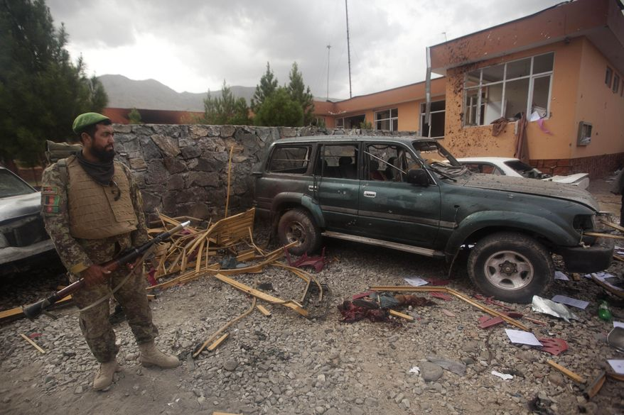 An Afghan soldier inspects a damaged vehicle after an attack on the provincial governor's compound in Parwan province's capital of Charikar, some 30 miles north of Kabul, Afghanistan, on Sunday, Aug. 14, 2011. (AP Photo/Dar Yasin)