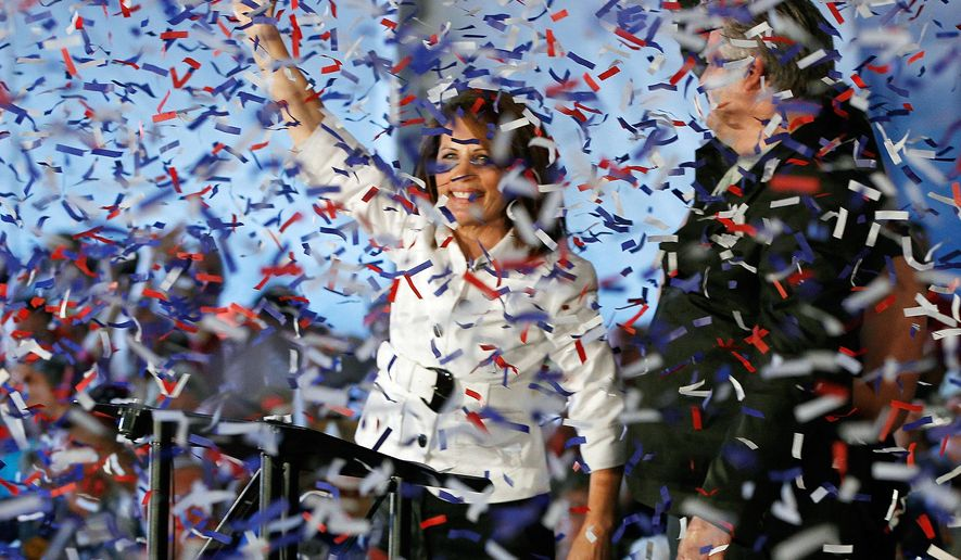 Confetti falls as Rep. Michele Bachmann, Minnesota Republican, and her husband, Marcus, rally supporters at the Iowa Republican Party's Straw Poll in Ames, Iowa, on Saturday, Aug. 13, 2011. (AP Photo/Charles Dharapak)