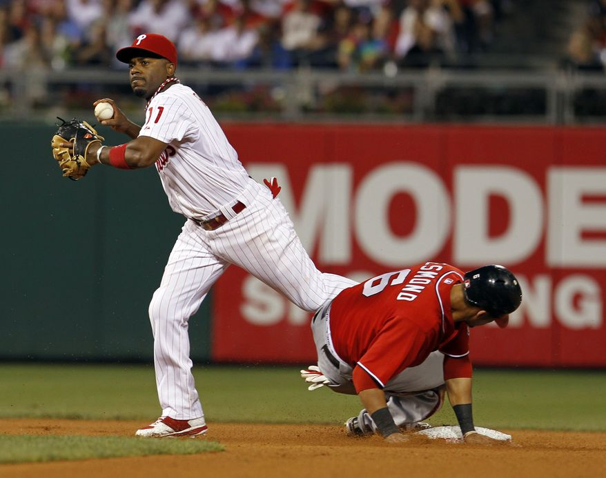 Ian Desmond (right) of the Washington Nationals is out at second base as he breaks up the double play by preventing the throw by Philadelphia Phillies shortstop Jimmy Rollins to get Alex Cora, who was safe at first, in the seventh inning of a baseball game on Saturday, Aug. 13, 2011, in Philadelphia. The Phillies won 11-3. (AP Photo/Alex Brandon)