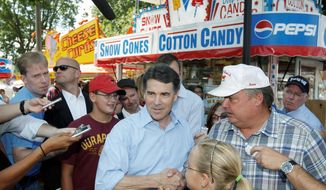 Texas Gov. Rick Perry greets visitors to the Iowa State Fair Monday, his first full day campaigning for the GOP presidential nomination. (Associated Press)