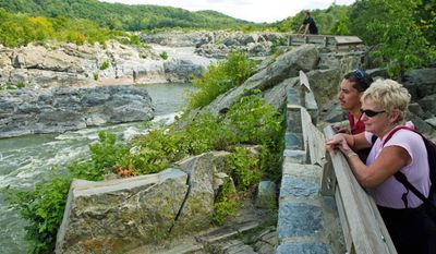 Antonio Rodriguez and Rutha Pryputniewicz, visiting from Wyoming, take in the view of the Potomac River from Great Falls National Park in McLean on Monday. (Drew Angerer/The Washington Times)