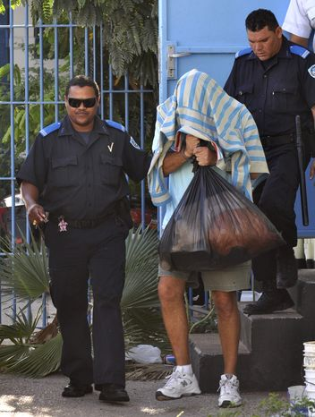 Gary V. Giordano, the U.S. citizen being held in the disappearance of 35-year-old Robyn Gardner, covers his head while being led to jail from a police station in San Nicolas, Aruba, Monday Aug. 15, 2011. A judge granted a request from Aruban prosecutors to extend the detention of Giordano, suspected in the death of his travel companion. (AP Photo/Pedro Famous Diaz)