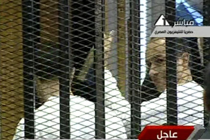 In this video image taken from Egyptian State Television, the sons of former Egyptian President Hosni Mubarak, Gamal (right) and Alaa, leave the defendants' cage in a Cairo courtroom on Monday, Aug. 15, 2011, after the presiding judge adjourned the trial until Sept. 5. (AP Photo/Egyptian State Television)