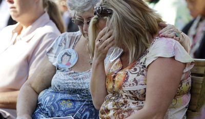 Judy Nicewinter (center) comforts Dianne Semento during a memorial service at the Indiana State Fair in Indianapolis on Monday, Aug. 15, 2011, for those killed in a weekend stage collapse. (AP Photo/Darron Cummings)