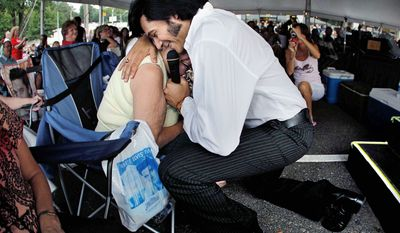 Elvis tribute artist Marcos Santos gives a personal serenade to Louise Smith of Southaven, Miss., during a performance in the Graceland Entertainment Pavilion on Monday night before the annual vigil.