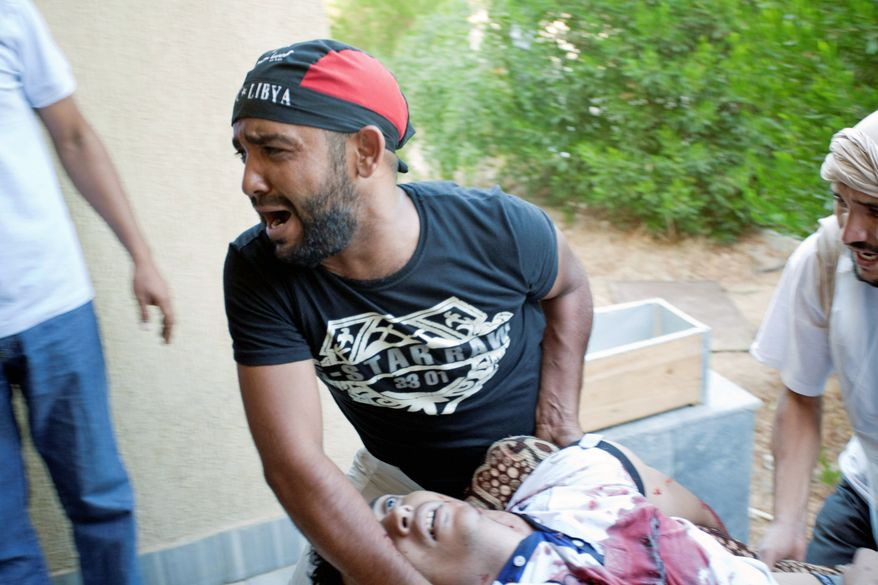 ASSOCIATED PRESS PHOTOGRAPHS A Libyan rebel reacts while helping to evacuate a wounded man after a shelling attack that struck mostly civilians in Zawiyah on Monday.
