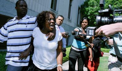 """Associated Press photographs Ablene Cooper and son Antonio Cooper leave the Hinds County courtroom in Jackson, Miss., on Tuesday, after a circuit judge dismissed her lawsuit against the author of the novel """"The Help."""" Ms. Cooper claims a main character, Aibileen, is based on her."""