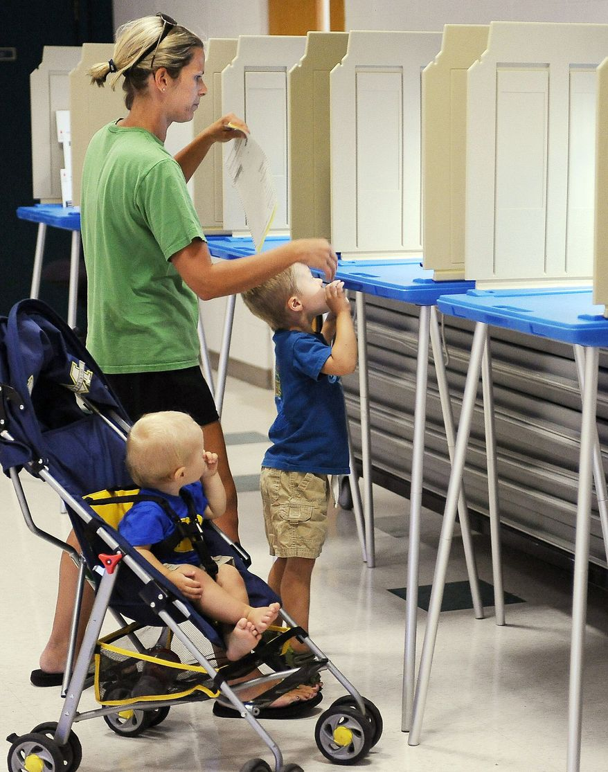 Molly Day takes her sons, Brady, 3, and Shane, 11 months, as she votes in Pleasant Prairie, Wis., on Tuesday. Wisconsin voters went to the polls for the third time in two months for a final state Senate recall vote. (Kenosa News via Associated Press)