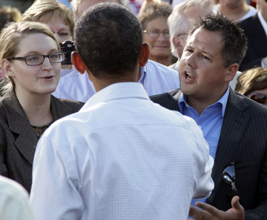 Ryan Rhodes (right) and another member of the Iowa Tea Party Revolution (left) speak Aug. 15, 2011, to President Obama at a town hall meeting in Decorah, Iowa, during the president's three-day economic bus tour. (Associated Press)